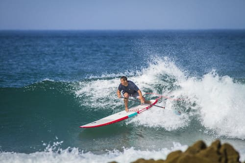 person doing stand up paddle with a nashwkell longboard