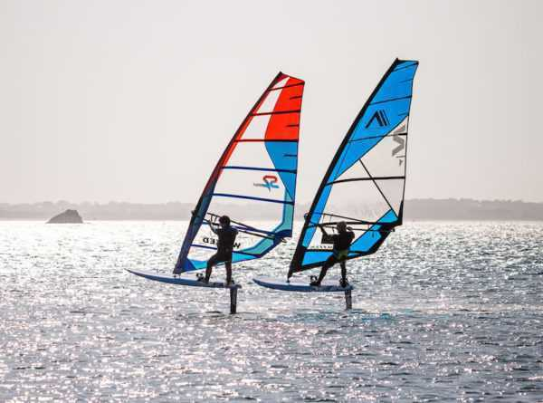 two individuals in foil windsurfing action