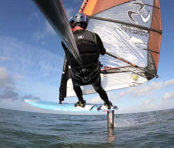 individual in action with foil windsurfing pole