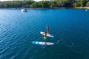 two individuals on stand up paddle nahskwell skool with calm water